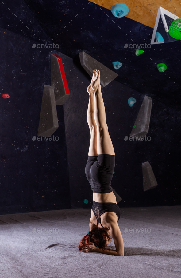Athletic young woman  practicing yoga in indoor climbing gym, doing headstand (Sirsasana) - Stock Photo - Images