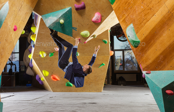 Young man in suit climbing difficult route on artificial wall in bouldering gym - Stock Photo - Images