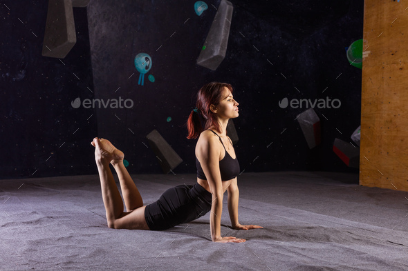 Athletic young woman practicing yoga in indoor climbing gym - Stock Photo - Images