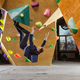Young man in suit climbing difficult route on artificial wall in bouldering gym - PhotoDune Item for Sale