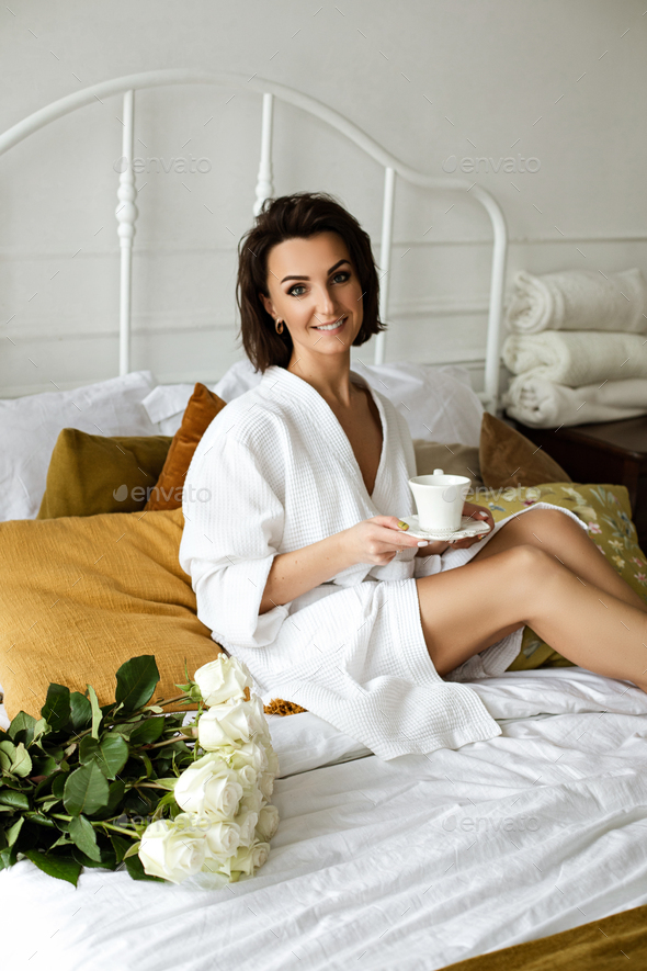 Beautiful woman with coffee in bed and roses - Stock Photo - Images