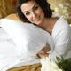Attractive smiling brunette hugging pillow on bed - PhotoDune Item for Sale