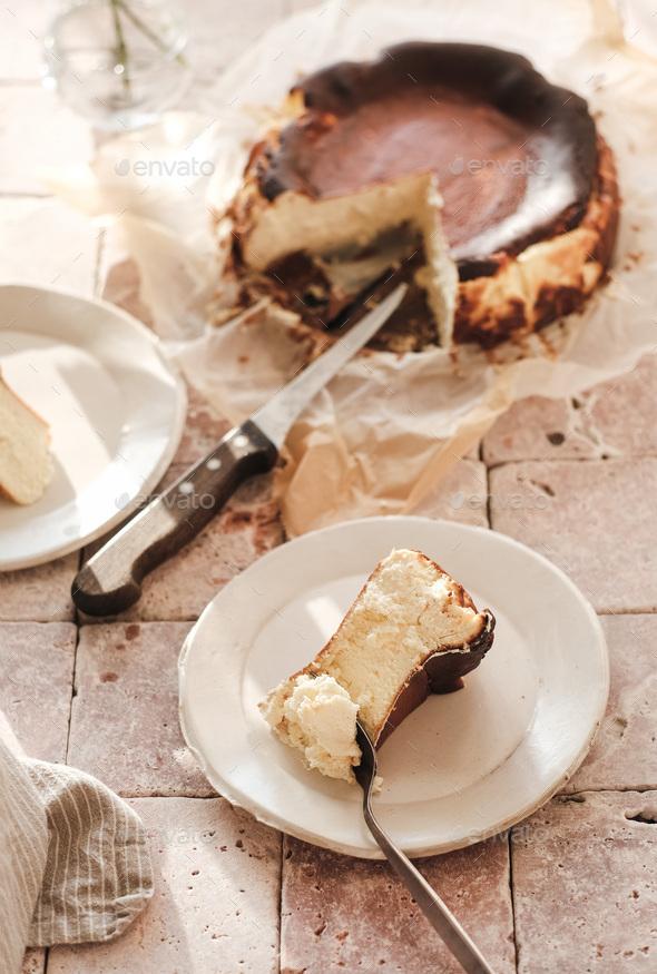 Piece of Homemade San Sebastian burnt cheesecake on white plate - Stock Photo - Images