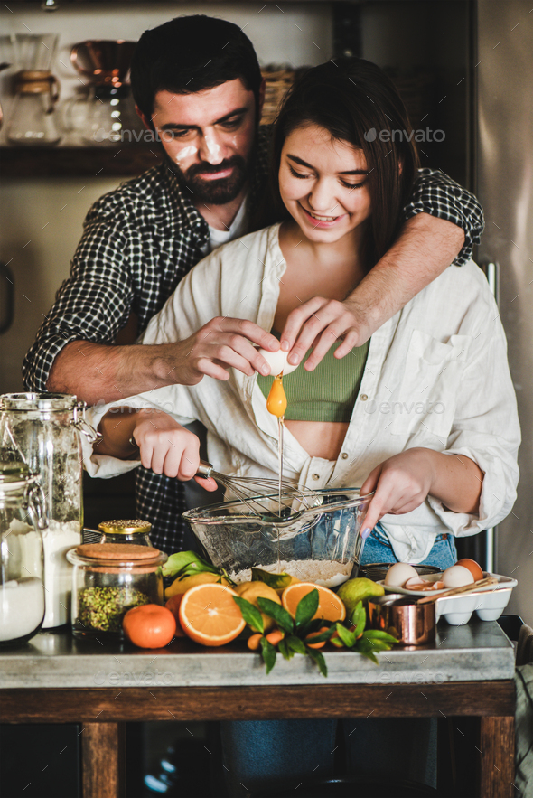 Young caucasian couple hugging baking holiday cake together at home - Stock Photo - Images