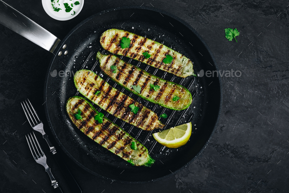 Grilled zucchini slices in cast iron pan on dark stone or concrete background - Stock Photo - Images