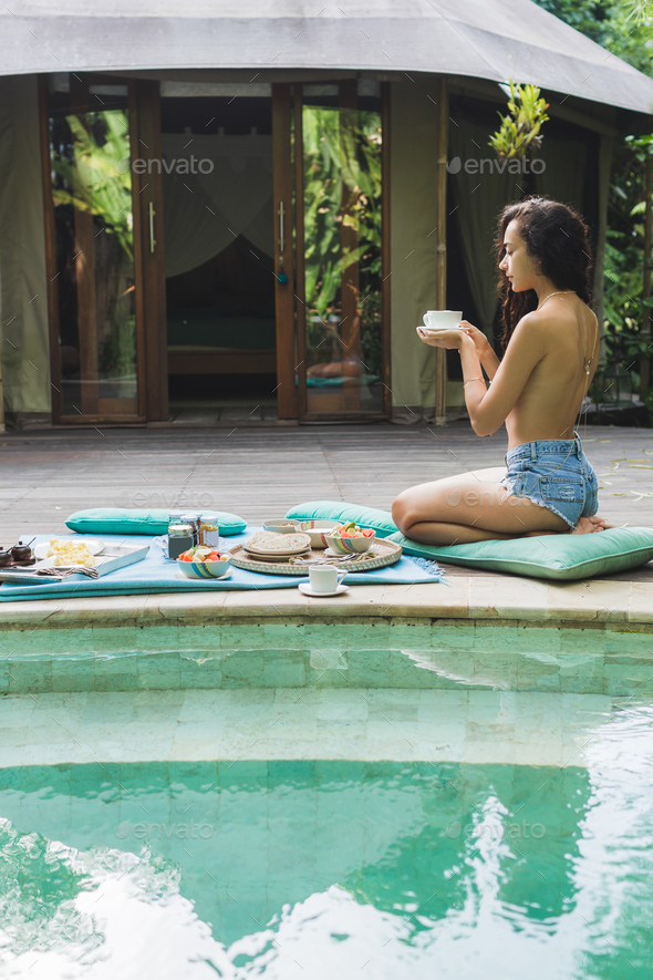 Woman enjoying fresh breakfast on private villa with swimming pool. Glamping tent style. Jeans short - Stock Photo - Images