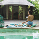Woman enjoying fresh breakfast on private villa with swimming pool. Glamping tent style. Jeans short - PhotoDune Item for Sale