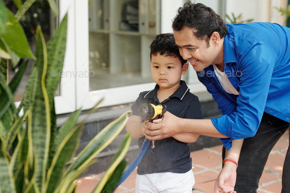 Dad and son watering plants - Stock Photo - Images