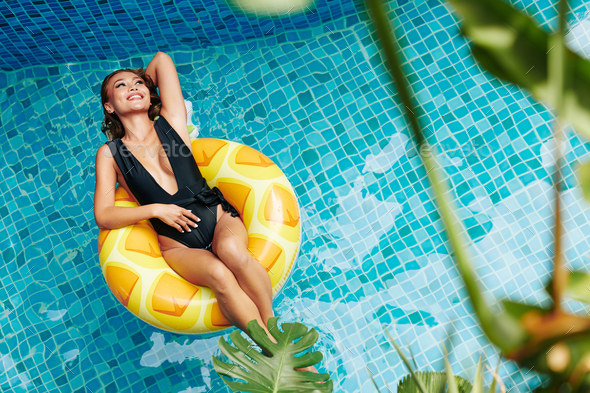 Attractive woman chilling in pool - Stock Photo - Images