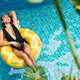 Attractive woman chilling in pool - PhotoDune Item for Sale