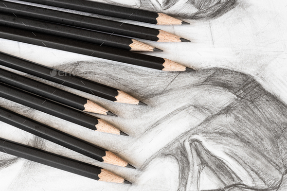 set of graphite pencils on drawing of male face - Stock Photo - Images