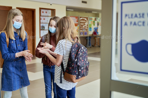 Group of schoolgirls wearing protective face masks disinfect their hands - Stock Photo - Images