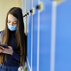 Schoolgirl standing next to lockers and using smartphone during pandemic - PhotoDune Item for Sale
