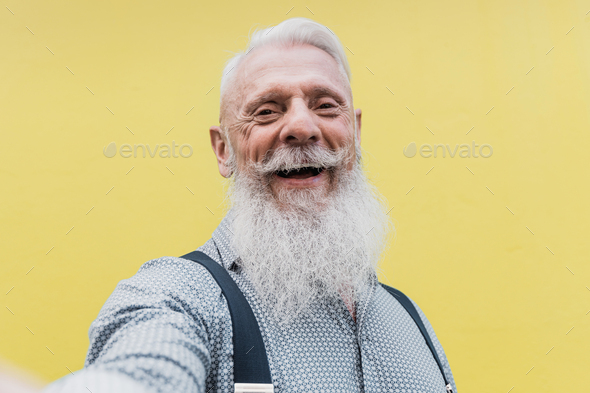 Happy hipster senior man taking a selfie outdoors in the city - Focus on face - Stock Photo - Images