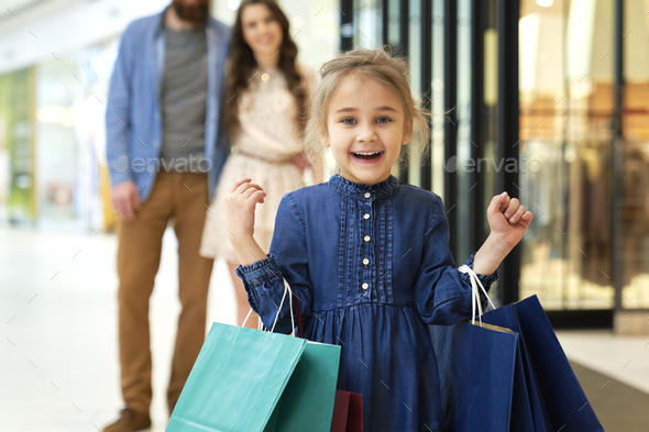 Portrait of happy girl during shopping at the mall - Stock Photo - Images