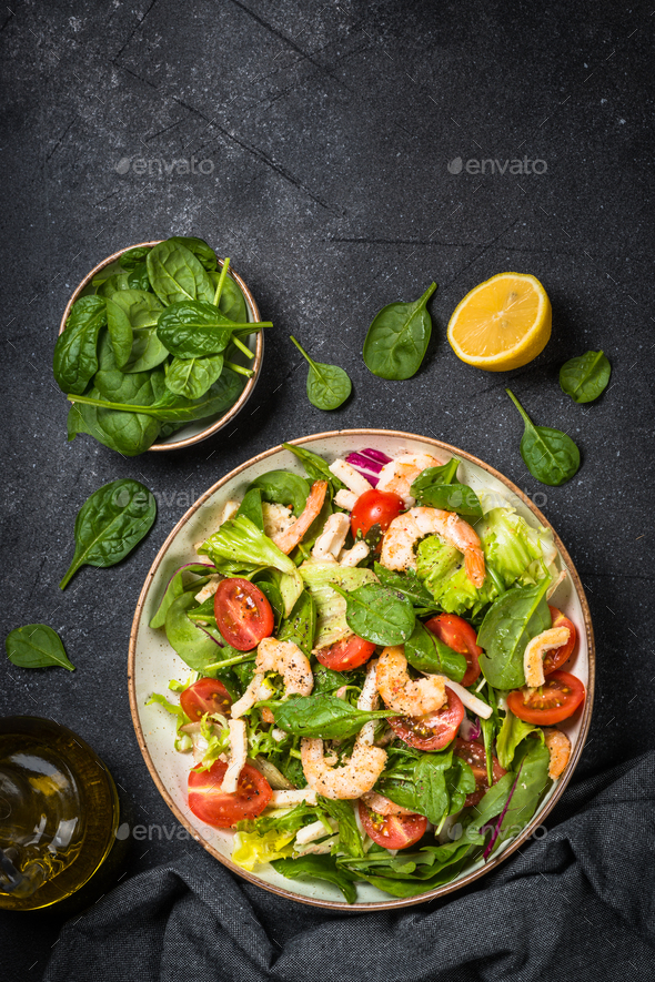 Shrimp salad with green leaves at stone table - Stock Photo - Images