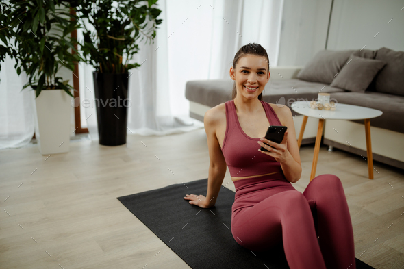 Active energtic sportswoman sit on mat use cellphone post sport comments in sportive blogs. - Stock Photo - Images
