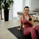 Active energtic sportswoman sit on mat use cellphone post sport comments in sportive blogs. - PhotoDune Item for Sale
