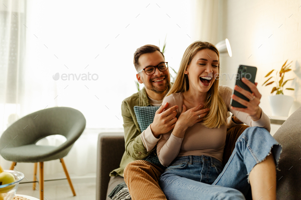 Excited millennial husband and wife relax on couch in kitchen feel euphoric win lottery online. - Stock Photo - Images