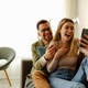 Excited millennial husband and wife relax on couch in kitchen feel euphoric win lottery online. - PhotoDune Item for Sale