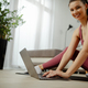 Close up photo of a sporty woman in sportswear is sitting on the floor, using a laptop at home. - PhotoDune Item for Sale
