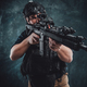 Dangerous and armed soldier aims a machine rifle in dark background - PhotoDune Item for Sale