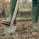 Farmer in rubber boots using spade gardening equipment in garden - PhotoDune Item for Sale
