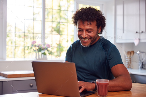 Mature Man Wearing Fitness Clothing At Home Logging Activity From Smart Watch Onto Laptop - Stock Photo - Images