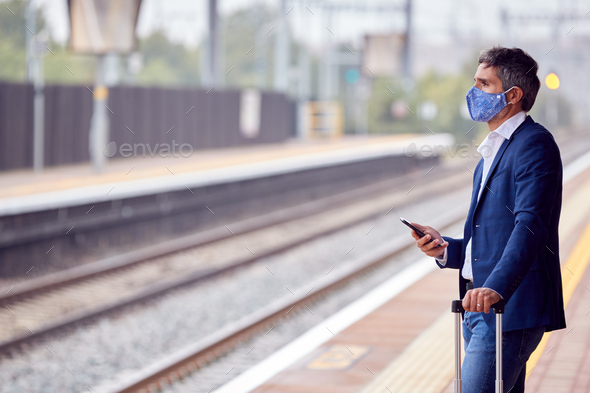 Businessman On Railway Platform With Mobile Phone Wearing PPE Face Mask During Health Pandemic - Stock Photo - Images