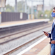 Businessman On Railway Platform With Mobile Phone Wearing PPE Face Mask During Health Pandemic - PhotoDune Item for Sale