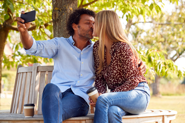 Kissing Mature Couple Posing For Selfie On Mobile Phone Sitting On Seat In Park - Stock Photo - Images