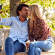 Kissing Mature Couple Posing For Selfie On Mobile Phone Sitting On Seat In Park - PhotoDune Item for Sale