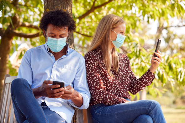 Couple Wearing Masks Meeting In Outdoor Park During Health Pandemic Looking At Mobile Phones - Stock Photo - Images