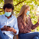 Couple Wearing Masks Meeting In Outdoor Park During Health Pandemic Looking At Mobile Phones - PhotoDune Item for Sale