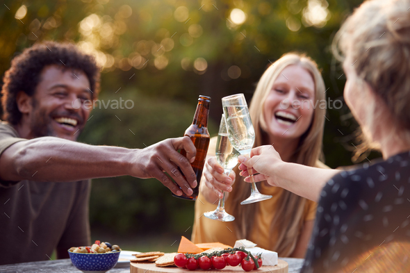 Group Of Friends Celebrating With Beer And Champagne As They Sit At Table In Garden With Snacks - Stock Photo - Images