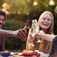 Group Of Friends Celebrating With Beer And Champagne As They Sit At Table In Garden With Snacks - PhotoDune Item for Sale