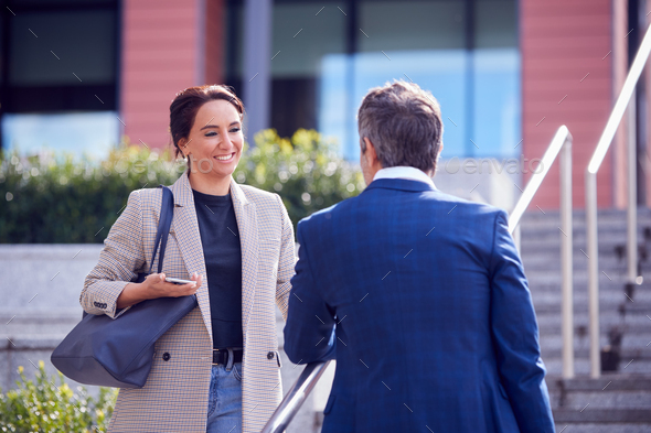 Businessman And Businesswoman Meeting Outdoors Standing On Steps And Talking - Stock Photo - Images