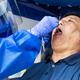Mature asian man doing covid 19 PCR swab test through the throat - PhotoDune Item for Sale