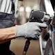 A young man is repairing a car at his work: car service and maintenance - PhotoDune Item for Sale