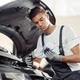 A young and attractive mechanic is checking an oil level of a car engine - PhotoDune Item for Sale