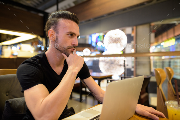 Man sitting at coffee shop using laptop computer and thinking - Stock Photo - Images