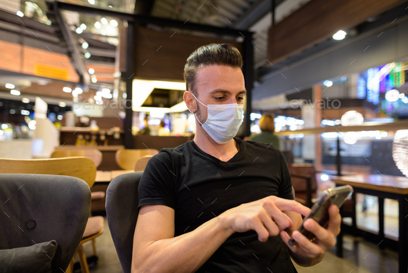 Man sitting at coffee shop while social distancing and using mobile phone and wearing face mask - Stock Photo - Images