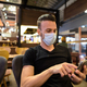 Man sitting at coffee shop while social distancing and using mobile phone and wearing face mask - PhotoDune Item for Sale