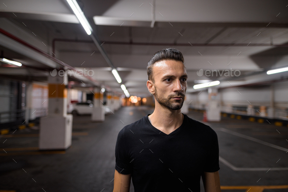 Portrait of handsome man at night at parking lot thinking - Stock Photo - Images