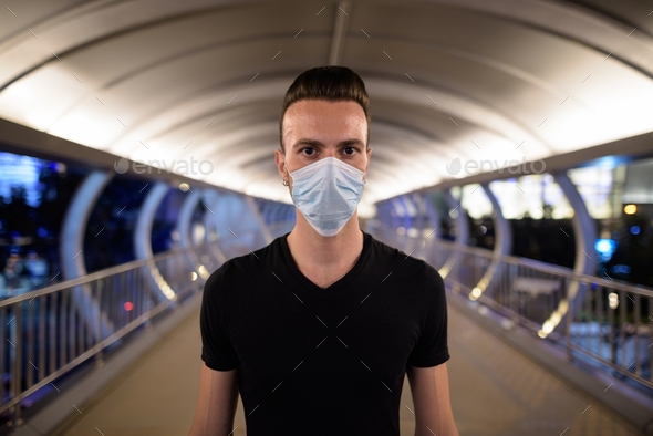Man at night standing in city wearing face mask - Stock Photo - Images