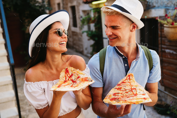 Group of friends eating pizza while traveling on vacation - Stock Photo - Images