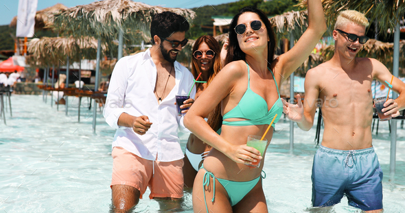 Happy friends having fun and dancing at summer beach party - Stock Photo - Images