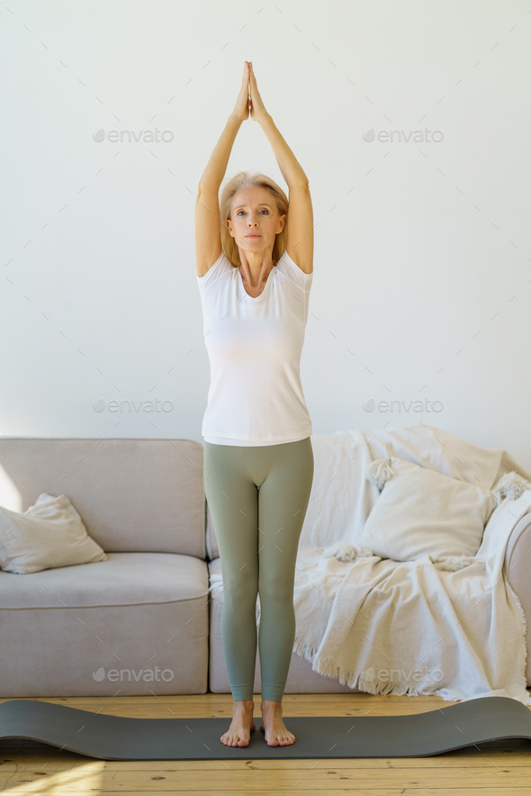 Active retired mature woman doing yoga exercise Surya Namaskar in living room at home - Stock Photo - Images