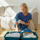 Mature woman packing her suitcase while preparing to travel during pandemic time - PhotoDune Item for Sale