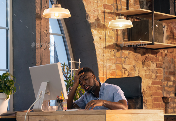 African businessman, manager working in modern office using devices and gadgets - Stock Photo - Images